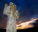 brightly lit stone cross